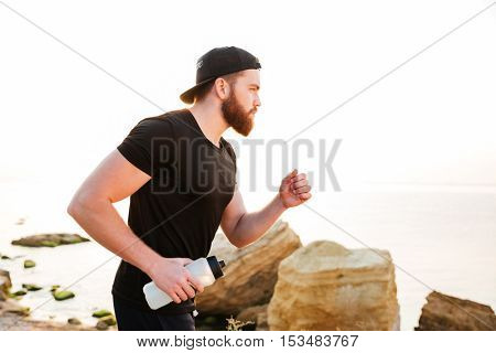 Confident young bearded man athlete running on the beach in the morning