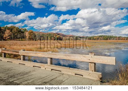 A wooden bridge crosses over a wildlife sanctuary overlooking beautiful autumn foliage and a cheerful cloudy sky reflecting in the water at the foothills of the Catskill Mountains in New York
