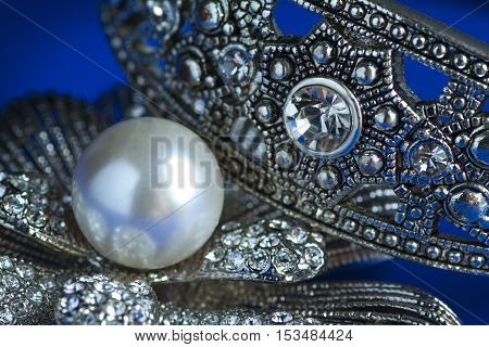 Pearl brooch isolated on a blue background