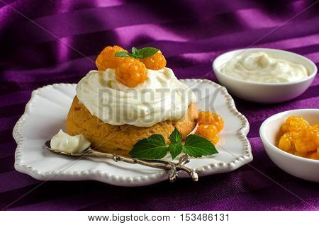 Cream cakes. Yellow cloudberries. Mint leaves. The desserts on the plate. Purple background. Silverware.