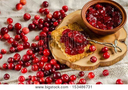 Red berries scattered on the table. Cranberry. Biscuits and jam from cranberries on the Board. A bright background.