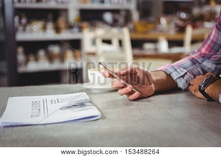 Hand of man holding mobile phone in cafeteria