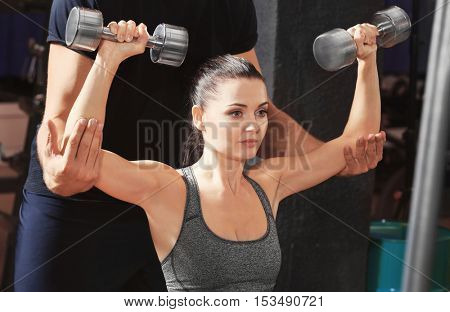 Personal coach helping woman to do exercises with dumbbells in gym