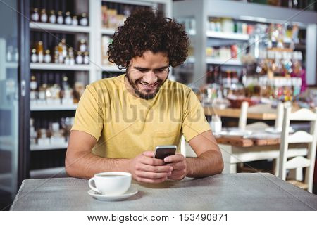Man using mobile phone in cafeteria