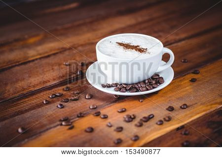 Close-up of coffee cup and beans on a table in cafeteria