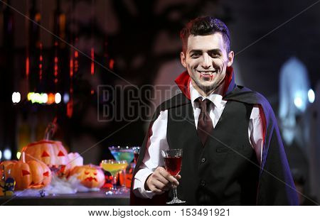 Young man dressed as vampire drinking cocktail at Halloween party