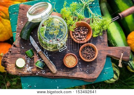 Preparation for pickled courgettes with spices in countryside at summer