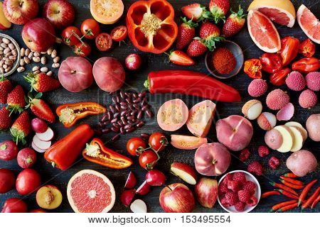Fresh vegetables and fruit in red colors, cut cross section flatlay overhead filled frame food layout
