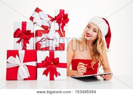 Smiling pretty young woman in santa claus costume with gift boxes writing on clipboard over white background