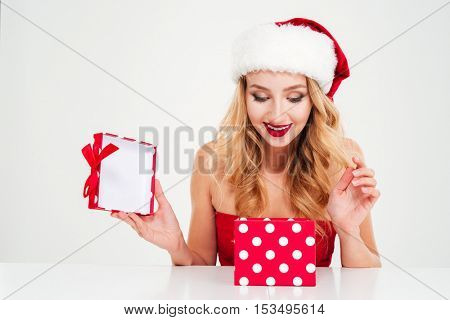 Cheerful charming young woman in santa claus costume looking inside gift box over white background