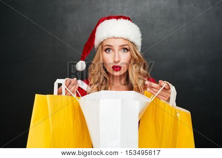 Amazed pretty young woman in santa claus costume holding shopping bags over black background