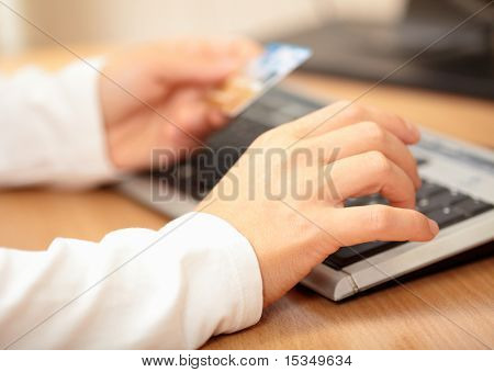 Hands holding credit card and keyboard. Shallow DOF