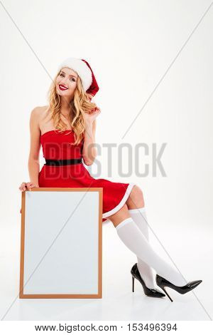 Happy attractive young woman in santa claus costume sitting and holding blank white board over white background