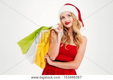 Happy lovely young woman in santa claus costume with shopping bags over white background
