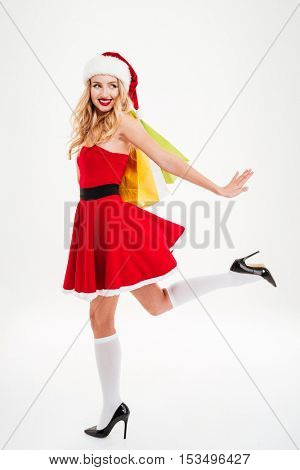 Full length of happy cute young woman in santa claus costume holding shopping bags and running over white background