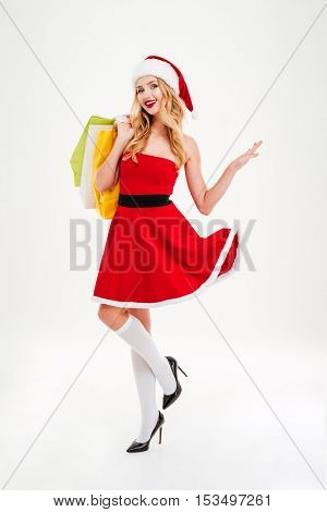 Cheerful pretty young woman in santa claus costume with shopping bags over white background