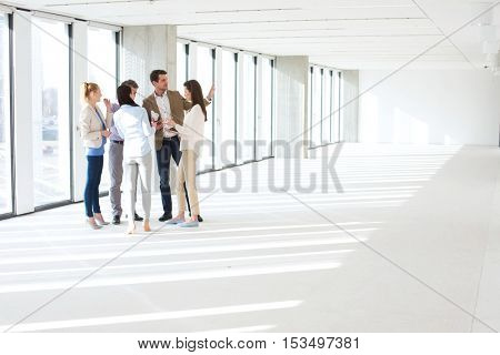 Full length of business people having discussion in empty office space