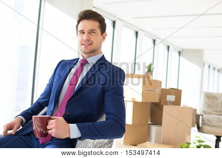 Portrait of young businessman holding coffee cup with moving boxes in background at office