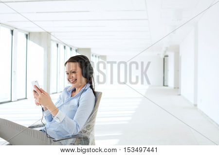 Smiling businesswoman listening music through headphones in empty office