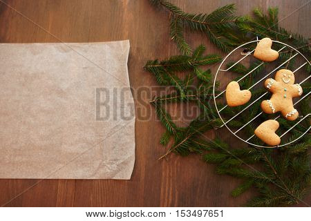 Blank culinary parchment with gingerbread cookies. Christmas culinary composition with pine-tree and free space for greeting or text
