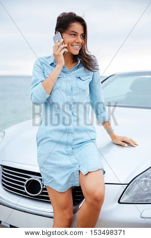 Cheerful smiling woman standing near car and using cellphone on the seaside