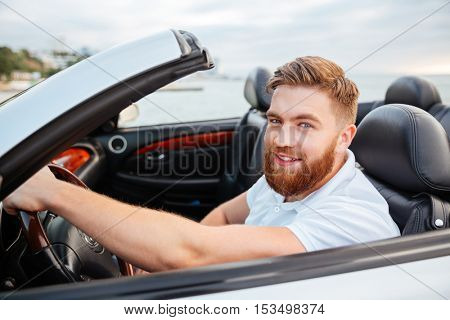 Portrait of young handsome smiling man sitting in his own car