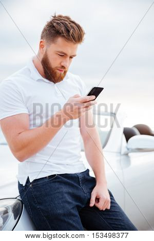 Concentrated young bearded man with smart phone leaning on his car