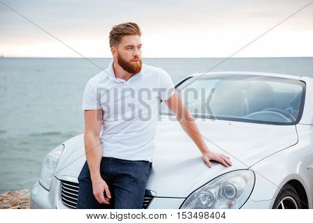 Young bearded man leaning on his car parked on beach