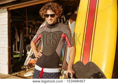 Happy young man surfer in sunglasses standing on the beach