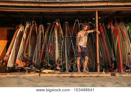 Handsome young man surfer standing near windsurfing equipment point on the beach