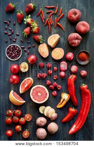 Collection of fresh organic red colored fruits and vegetables, beans strawberry chilli peach grapefruit tomato potato raspberry plum pepper paprika