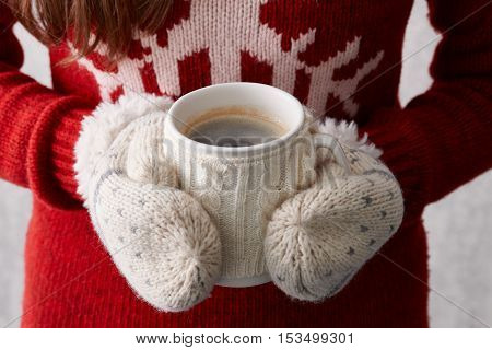Girl in mittens holding winter cup of hot coffee, close up view