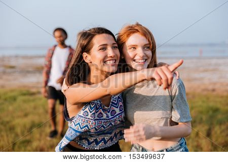 Two smiling beautiful young women looking and pointing away outdoors
