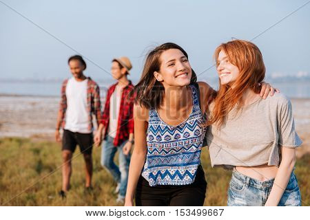 Two cheerful girls walking and laughing while their boyfriends talking outdoors