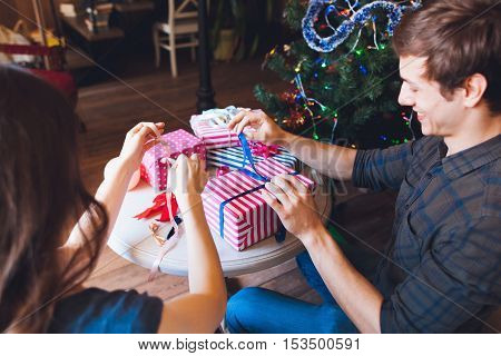 Smiling man packing presents with wife. Preparing for Christmas holidays. Happy family, X-mas celebration, joy, surprise, love concept