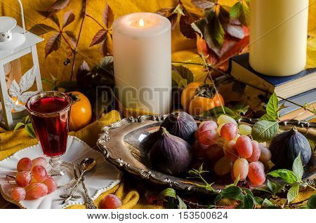 Autumn harvest. Fruit on a vintage silver platter. Grapes figs persimmons. Candles.Books.Vintage shot glass with red drink.Silverware. Fallen yellow leaves.