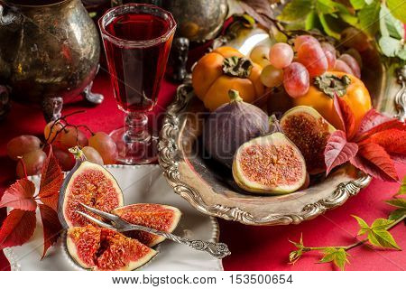 Cut ripe figs on a white vintage plate. The brandy in the glass. Persimmon figs grapes on a silver platter. Silverware. Vintage. Autumn crimson leaves. The red background.