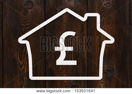 Paper house with pound sterling sign inside. Housing, money concept. Dark wooden background. Abstract conceptual image