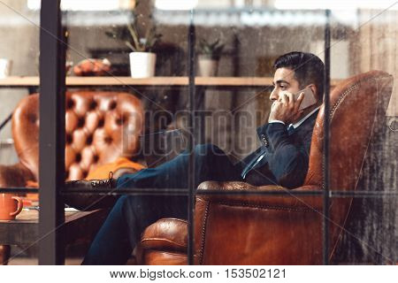 Successful businessman sitting in firm. Side view on man talking on phone. Professional activity. Advising. Counseling. Trading.