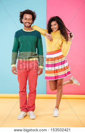 Happy playful african young couple standing and winking over colorful background