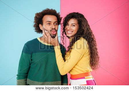 Cute smiling african american young couple showing tongue and having fun