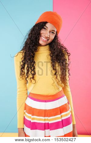 Happy beautiful african young woman in bright clothes over colorful background