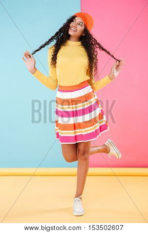 Full length of cheerful playful african young woman in bright clothes and hat