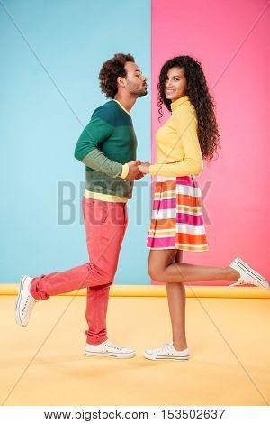 Cute african american young couple standing and kissing over colorful background