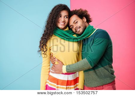 Happy african young couple in scarf standing and hugging over colorful background