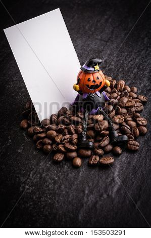 Red gift box and halloween toy decorate with roasted coffee beans on dark background can be used as a background