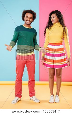 Full length of happy beautiful african young couple in bright clothes standing over colorful background