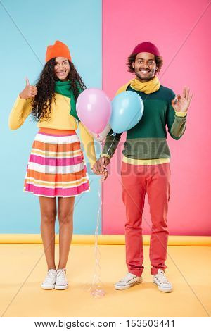 Smiling african young couple in hats and scarves with balloons showing thumbs up and ok sign