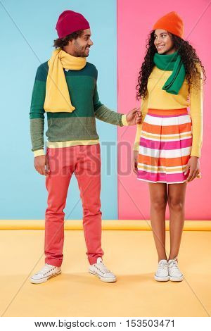 Happy african young couple in hats and scarves standing over colorful background