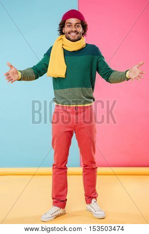 Cheerful african american young man in hat and scarf showing welcome gesture